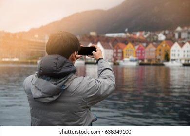 A tourist male taking photo with mobile phone of Bergen attraction, Norway