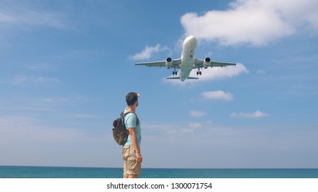 Tourist man with backpack welcomes airplane for travel. Hello vacation concept.