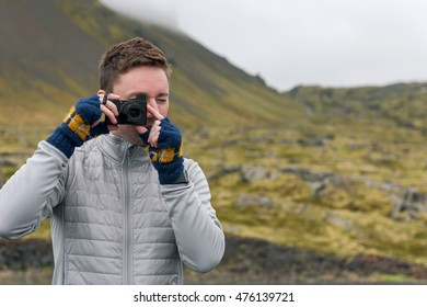 Tourist man with camera shooting mountain landscape in Iceland