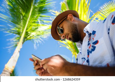 Tourist man dressed up in floral shirt with sun glasses and hat, tourist man under the coconut trees while looking at his cell phone