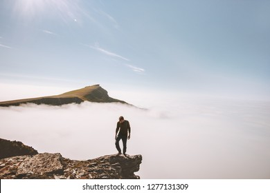 Tourist man exploring mountains over clouds active adventure solo traveling lifestyle summer vacations outdoor