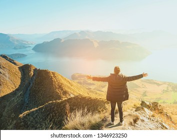 A tourist man is hiking to the top of the mountain with lake and mountain background. Powerful moment and feeling happy of traveling.