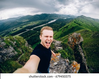 tourist man holds an action camera and takes pictures of himself against the background of mountains, forests, Gorny Altai, Russia. concept makes selfie