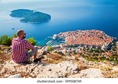 tourist man looking down to the Old Town of Dubrovnik, sitting on the mountain above the city, Croatia