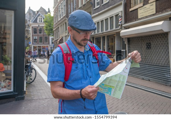 a tourist man looks at a map on a street in Amsterdam