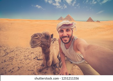Tourist man on camel in Giza. happy man take selfie photo near Pyramid of Khafre, Egypt