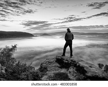 Tourist man on rock empire  is watching over creamy mist and foggy morning valley to Sun. Beautiful autumn morning