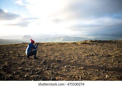 Tourist man shooting with his camera nature mountain landscape. Dyrholaey peninsula in Iceland