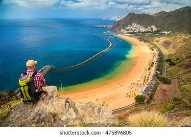 tourist man sitting on the edge of a cliff, enjoying amazing sea view of the beach Playa de Las Teresitas in Tenerife, Canary Islands, Spain