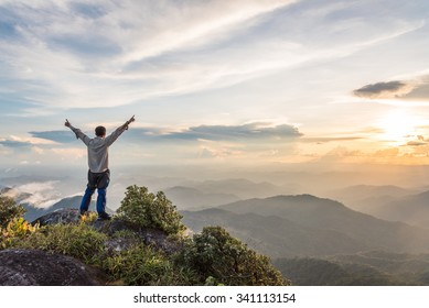 Tourist man spread hand on top of a mountain enjoying valley view
