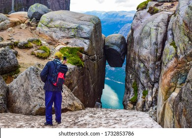 Tourist man takes a photo of the most dangerous stone in the world of Kjeragbolten. Kjeragbolten is a rock stuck at an altitude of 984 meters above Lysefjorden on mountain Kjerag, Norway.