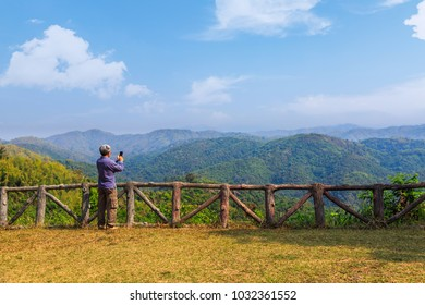 Tourist man takes photograph of nature scenery with mobile phone, Phetchabun province, Thailand