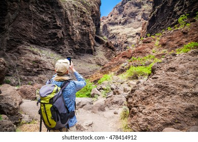 tourist man taking a photo of the beautiful famous canyon Masca in Tenerife, Canary islands, Spain
