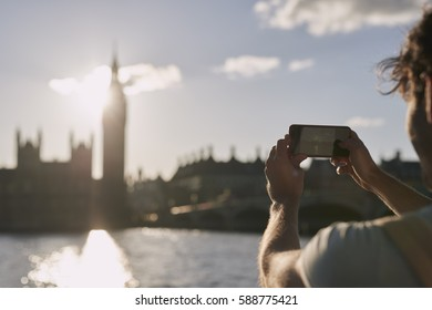 Tourist man taking photo of Big Ben London with smart phone technology for social media at sunset