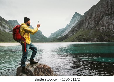 Tourist Man taking selfie by smartphone sightseeing Lofoten islands beach Travel lifestyle wanderlust concept adventure outdoor summer vacations