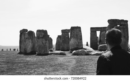 A tourist man  watching the Stonehenge in black and white.
