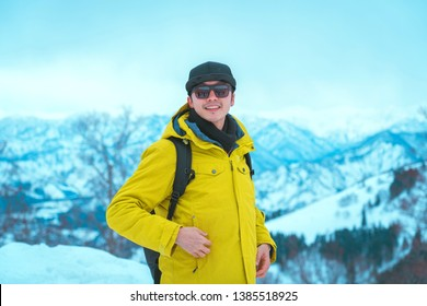 tourist man in wear yellow jacket and sunglasses standing on snow mountain
