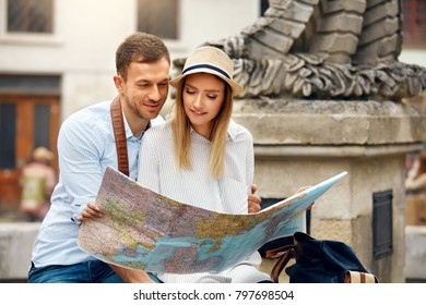 Tourist Man And Woman With Map On City Street. Beautiful Smiling Couple In Love Holding Map In Hands While Traveling Together. Travel Concept. High Resolution.