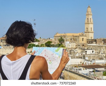 Tourist with a map in his hans in front of Lecce rooftop view with the Campanile, bell tower, of Cattedrale metropolitana di Santa Maria Assunta cathedral in background. Lecce, Puglia, Italy.