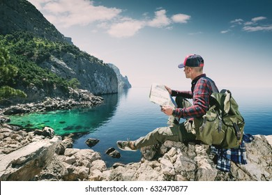 Tourist with a map in the mountains by the sea travels the wilderness. Adventures of a man with a backpack on the island. The hiker relaxes. Young backpacker.