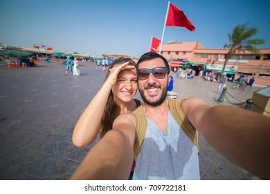 Tourist in marrakech in Jamaa el-Fna market taking photo selfie