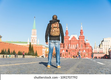 Tourist in Moscow, Red Square, looking at buildings. Man travelling to the capital city of Russia and visiting the main landmarks and showing the back to the camera. Travel and architecture concepts