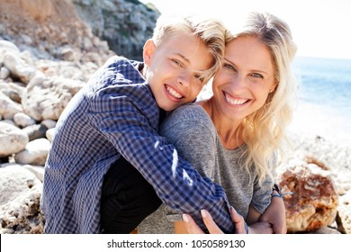 Tourist mother and son on beach holiday, hugging looking smiling in nature, closeness sunny outdoors. Family together, activities day out enjoying travel recreation leisure lifestyle, joyful portrait.