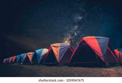 Tourist near his camp tent at night under a sky full of stars. Orange illuminated tent