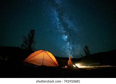 Tourist near his camp tent at night under a sky full of stars. Orange illuminated tent.