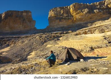Tourist next to a tent before a natural gate La Breche de Roland