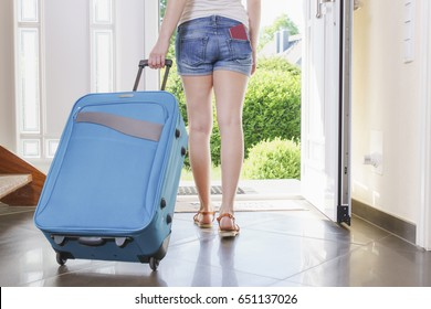 tourist nn T-shirt, shorts and sandals with blue vacation suitcase exits through the front door.