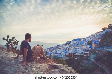 Tourist observing a panoramic view of blue city of Chefchaouen from point of view, Morocco