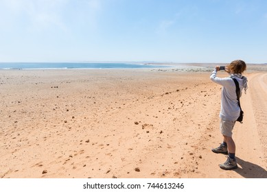 Tourist on the beach photographing with smart phone the Atlantic ocean at Cape Cross, Namibia. Clear blue sky.