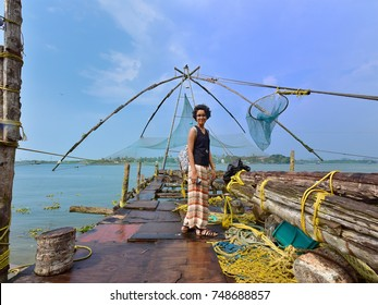 A tourist on the Chinese fishing net at Fort Kochi. Weight of a man walking along the main beam is sufficient to lower the net into the sea.