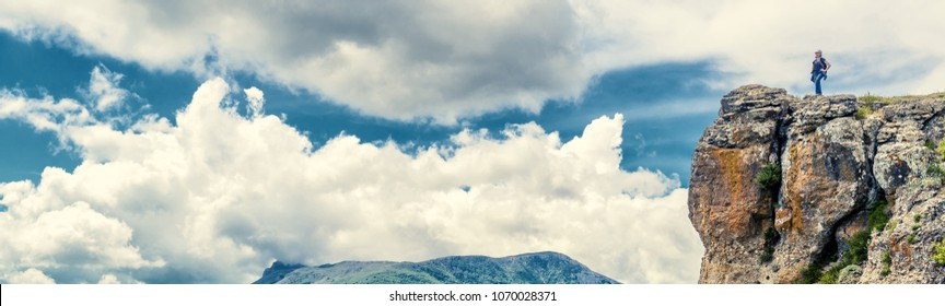 Tourist on Demerdji mountain in Crimea, Russia. Woman traveler on top of a mountain on the clouds background. Horizontal banner of travel concept for website header. Sunny summer panoramic view.