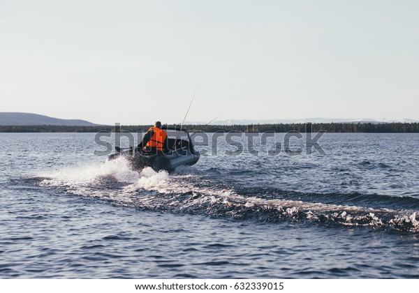 Tourist on a Fishing Trip in a Life Jacket Driving and Maneuvering on Inflatable Boat