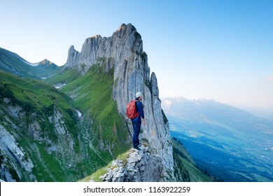 Tourist on the high rocks background. Sport and active life concept. Adventure and travel in the mountain region in the Switzerland mountains.