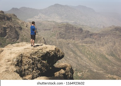 Tourist on mountain edge facing great landscape views. Young man on blue t shirt standing on top of rock on sunny day in Roque Nublo. Adventure, explore, freedom, visionary, solitude concepts