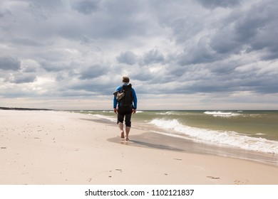 Tourist on a sandy beaches by the Baltic sea in Poland with dramatic sky in the background.