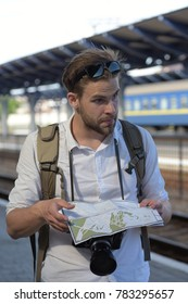 Tourist on the street looking at a guide. Traveller on train station trying to find his way. Man with surprised face on blurred station background. Travelling and navigation concept.