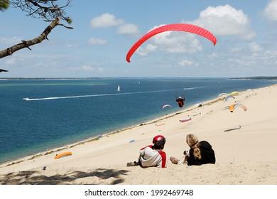 Touriste en vacances à la dune de Pyla, observant les parapents voler dans la baie d'Arcachon en France