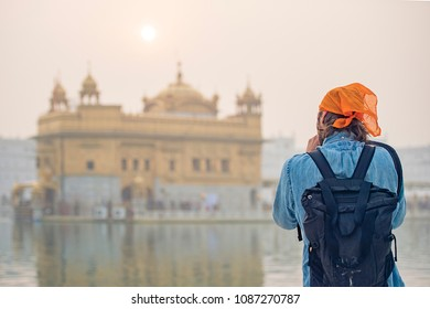 A tourist with an orange bandana is taking a picture at the beautiful Golden Temple of Amritsar, Punjab, India.