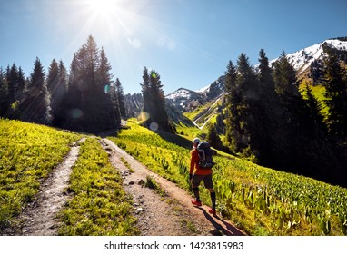 Tourist in orange shirt with backpack walking in the mountains. Outdoor travel concept