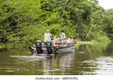 Tourist out for boat excursion along the Yana Yaquillo tributary of the Amazon with tour guides