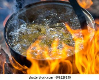 Tourist pan on bonfire. Preparing soup. Boiled water with potato closeup view.