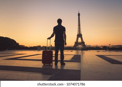 tourist in Paris looking at Eiffel Tower, silhouette of man with luggage travel to France