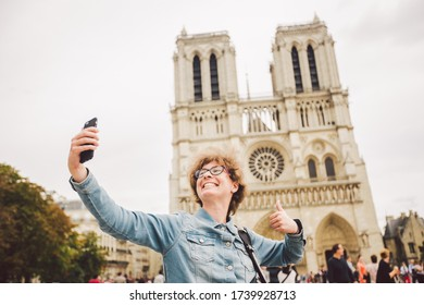 Tourist in Paris making funny selfie near Notre Dame Cathedral. Beautiful young Caucasian tourist woman with backpack in Paris making funny selfie hand holding phone, photo near Notre Dame Cathedral.