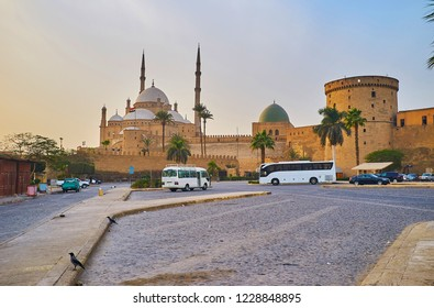 The tourist parking in front of medieval Saladin Citadel with a view on its fortifications and historic mosques - Alabaster and Al-Nasir Muhammad, Cairo, Egypt.