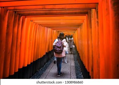 Tourist people visit torii gates of Fushimi Inari Taisha shrine in Kyoto, Japan. Motion visitors walk throughred torii wooden gate.