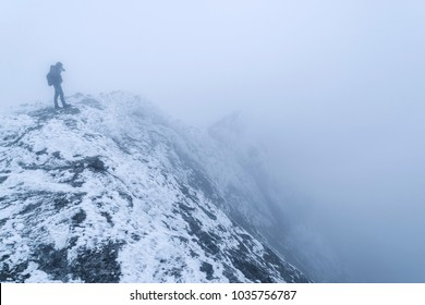A tourist photographer at the edge of a snow-covered rock in a fog takes pictures